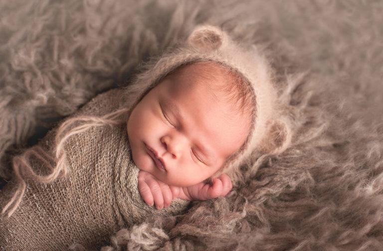 baby boy in bear hat on neutral grey fur during newborn photos on long island studio